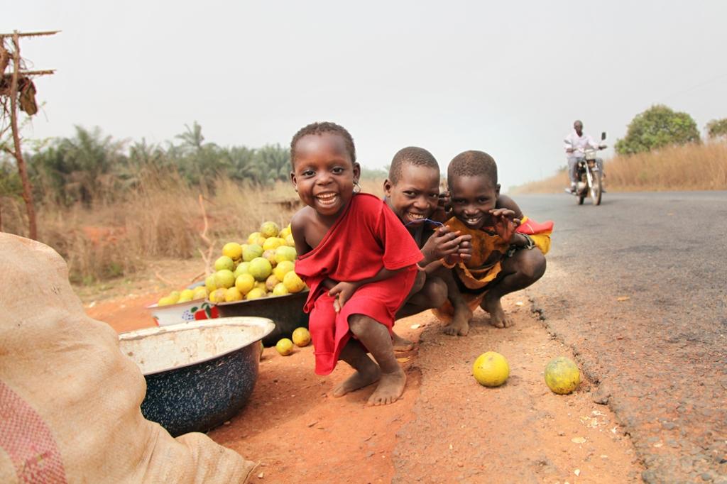"""Nogle børn foran en butik med appelsiner på landevejen mellem Bohicon og Cové. Den lille pige har """"skæremærker"""" på kinderne - ar som viser hvilken stamme hun hører til. Vejen er finansieret af Danida og blev bygget færdig i 2006. Den har betydet m"""