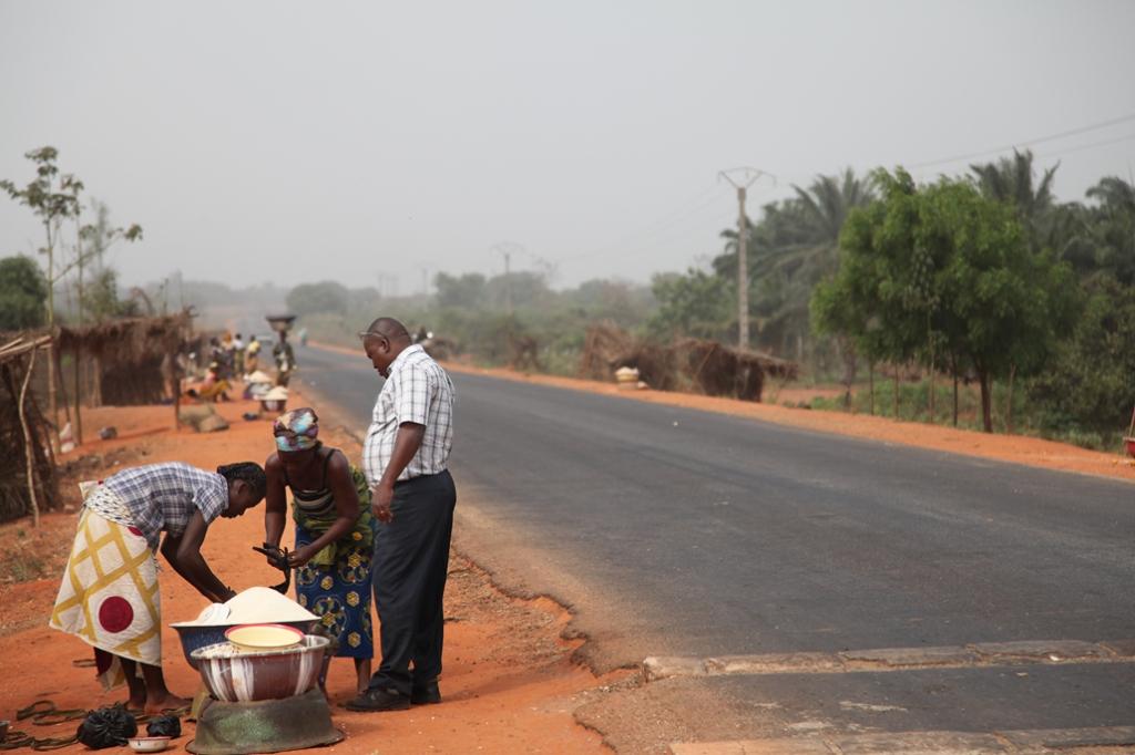 To kvinder er i gang med at sælge varer til en mand. Deres butik ligger ved landevejen mellem Bohicon og Cové som er finansieret af Danida og blev bygget færdig i 2006. Vejen har betydet meget mere trafik og dermed meget mere handel. Det er nemmere at